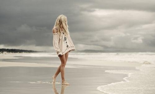 girl walking on the gray beach