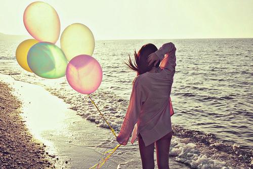 chica con globos caminando en la playa