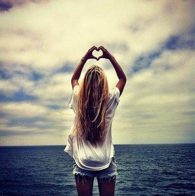 chica haciendo el símbolo del corazón al mar
