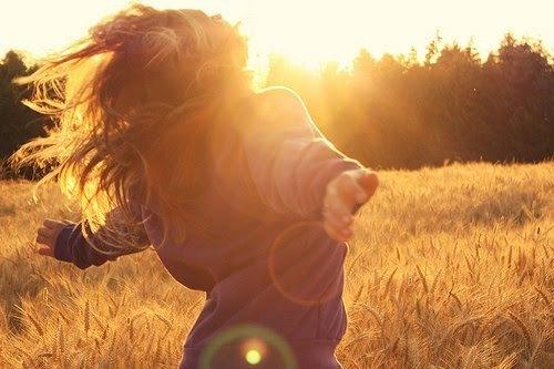 chica libre con los brazos extendidos hacia el sol