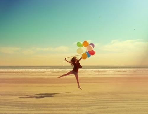 chica libre en la playa saltando con globos
