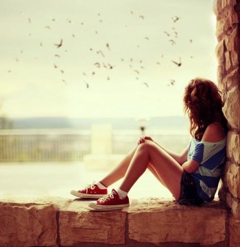 chica sentada en la ventana viendo a las aves