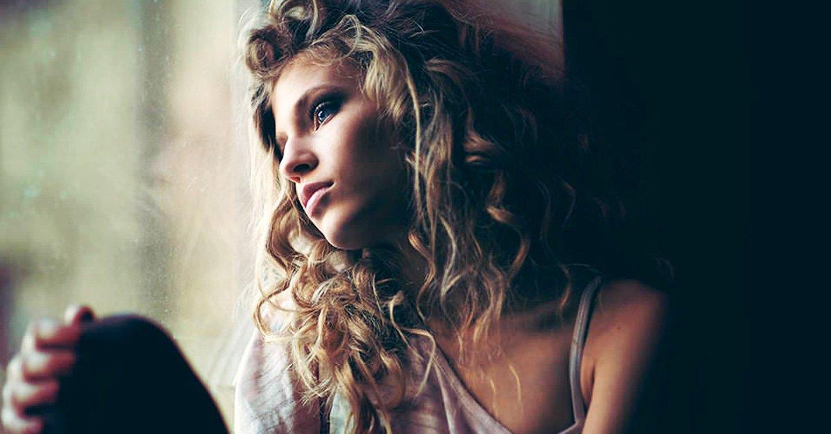 chica triste viendo por la ventana