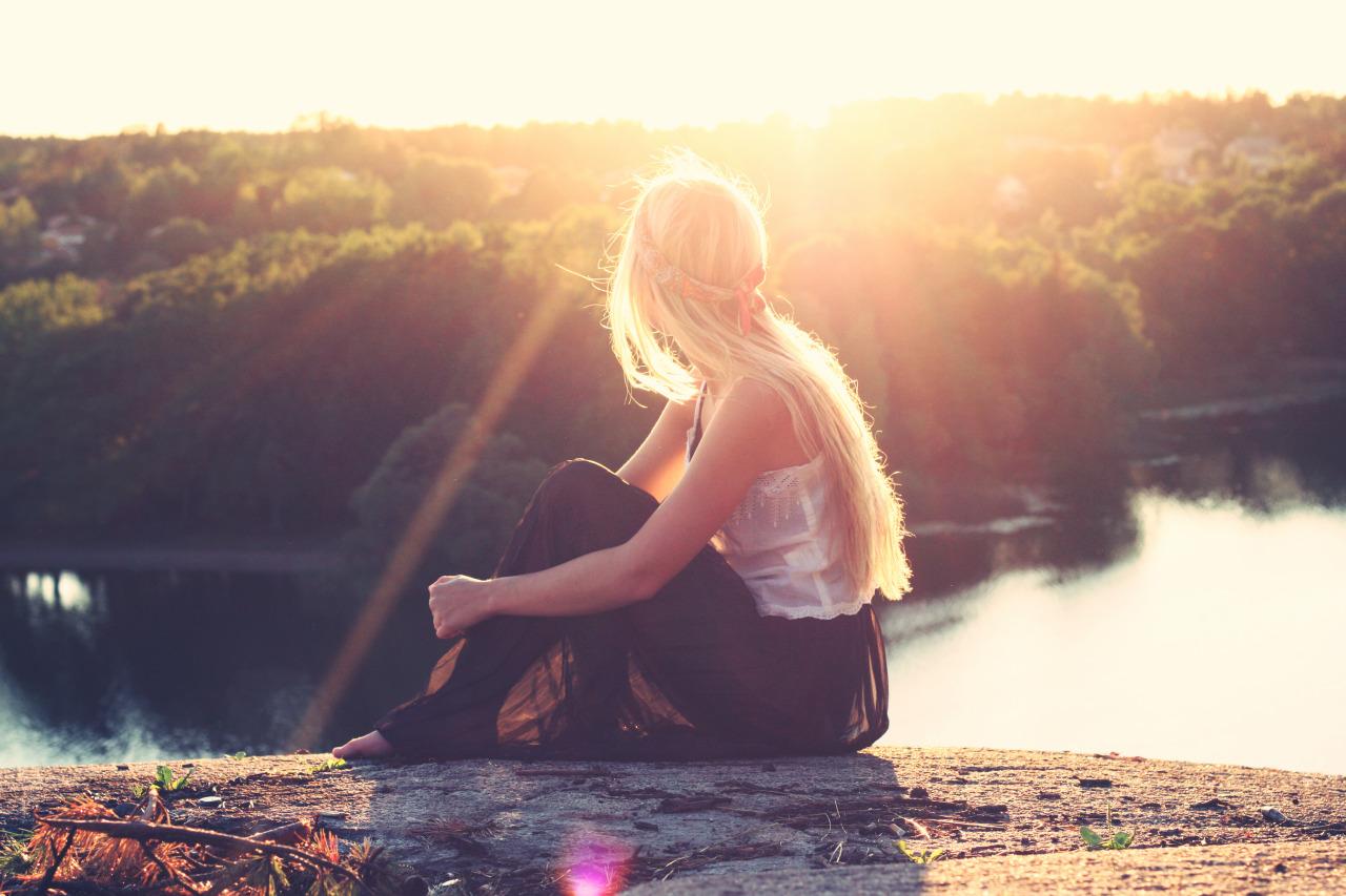 chica viendo al sol en el lago