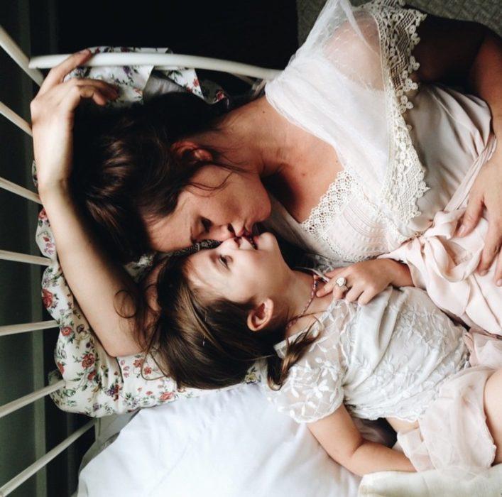 Madre e hija recostadas en la cama