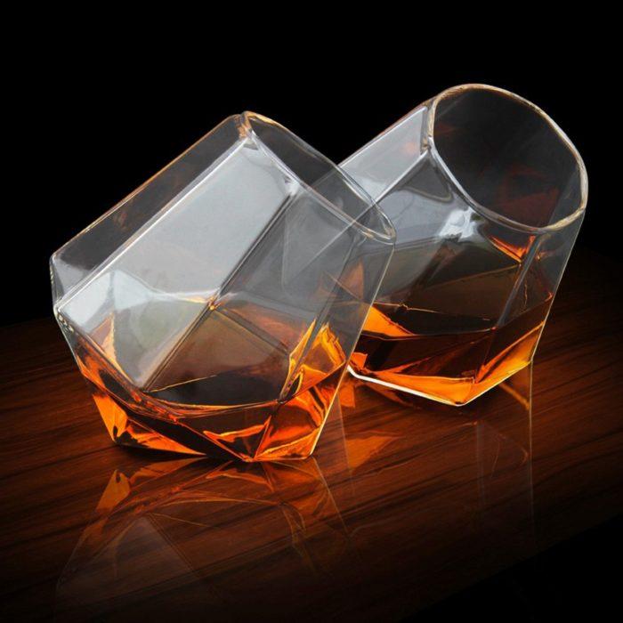 dos copas de vidrio en forma de diamante con alcohol