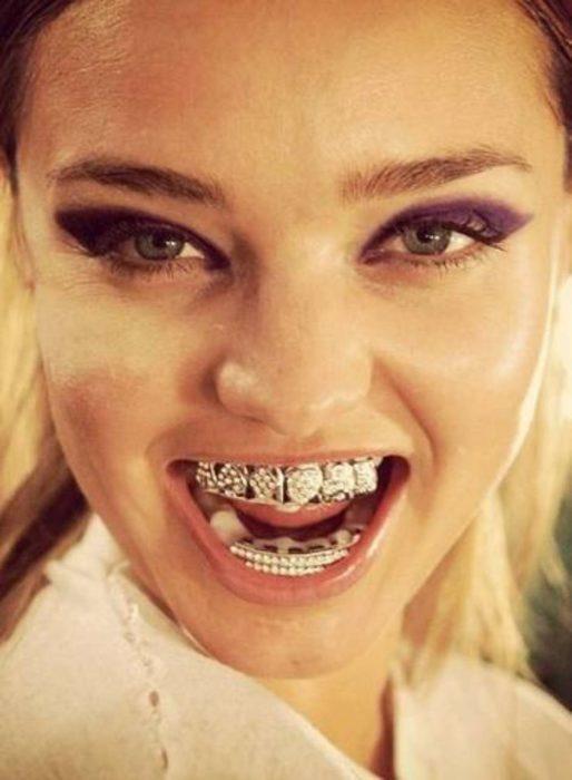 mujer sonriendo con joyas en sus dientes