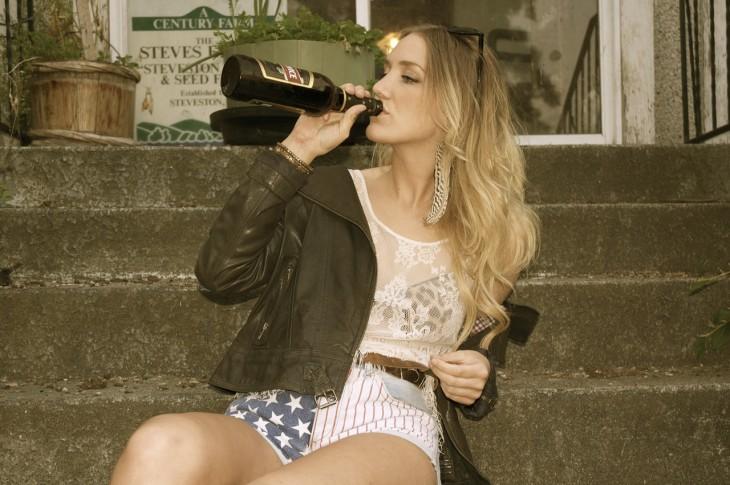 mujer bebiendo vino directo de la botella
