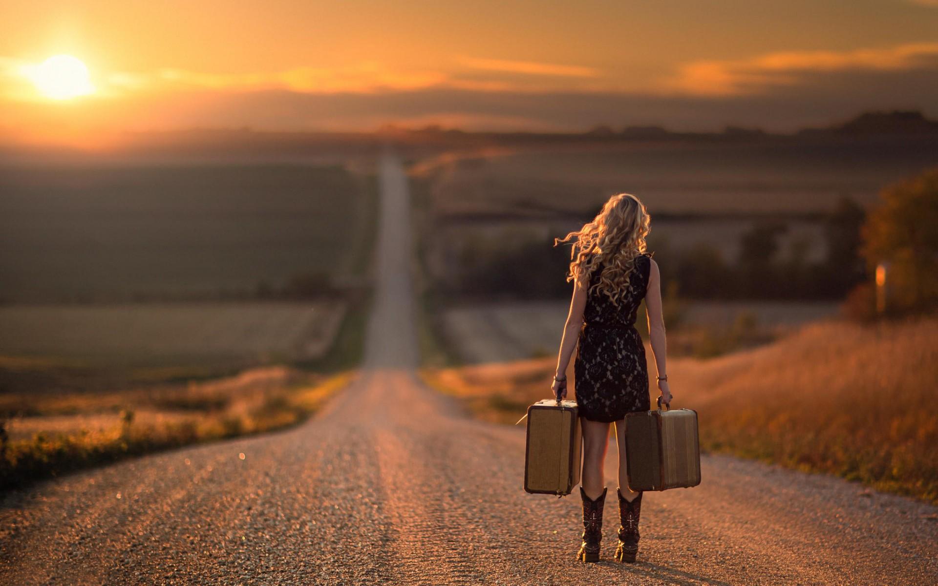 mujer camina por la carretera con dos maletas