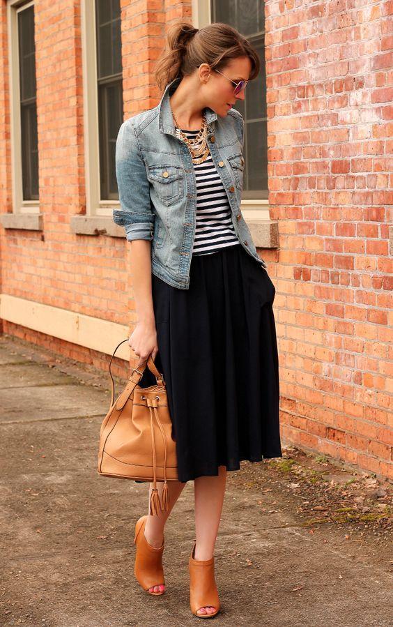mujer con blusa de rayas y chamarra de mezclilla y falda