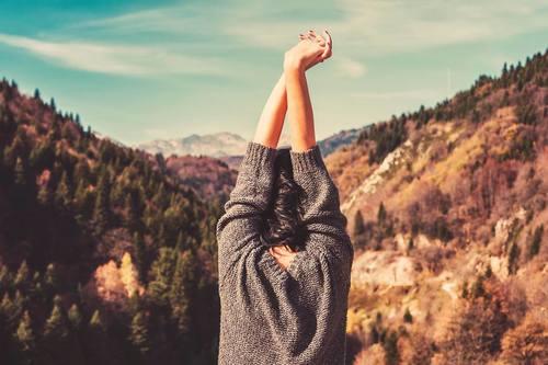 mujer libre entre las montañas con los brazos arriba y cruzados