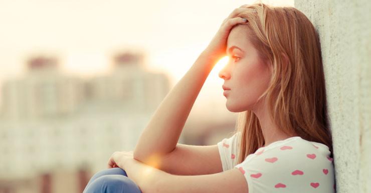 mujer sentada a contra luz pensando