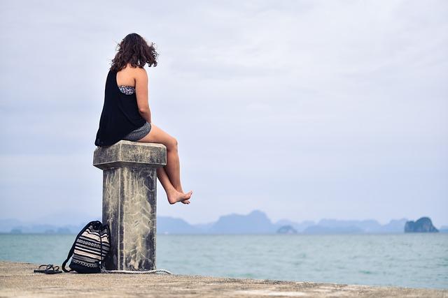 mujer sentada en el muelle frente al mar