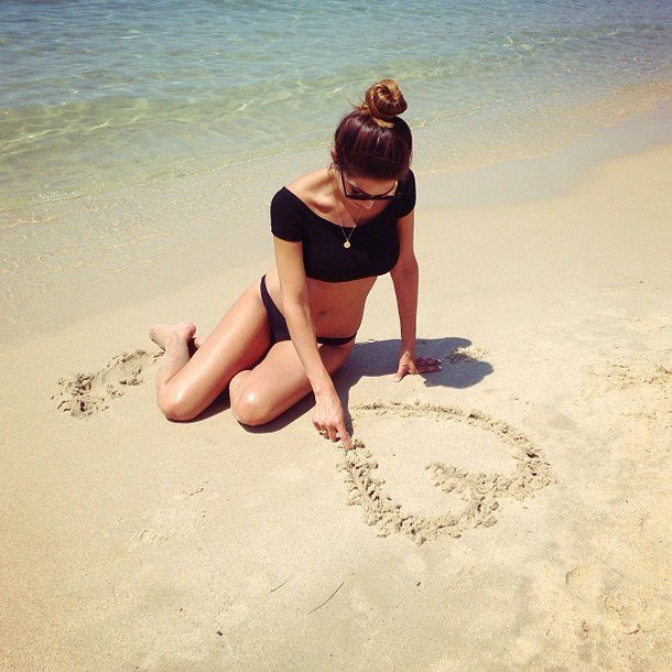 mujer sentada en la playa dibujando un corazón
