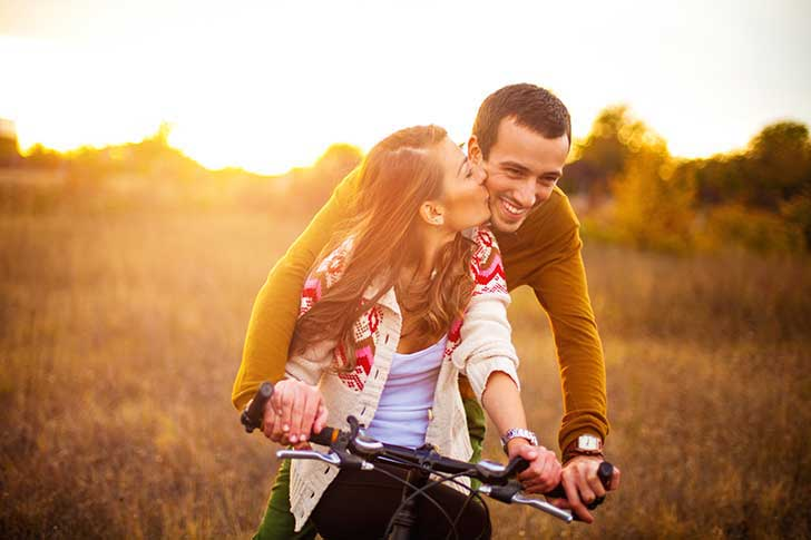 novia besando a su novio en bicicleta