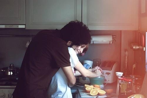 novio abrazando a su novia por la espalda en la cocina