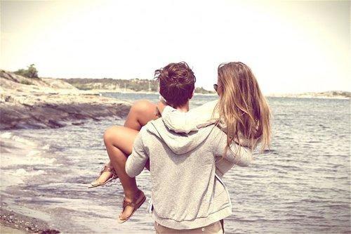 novio cargando a su novia por la playa