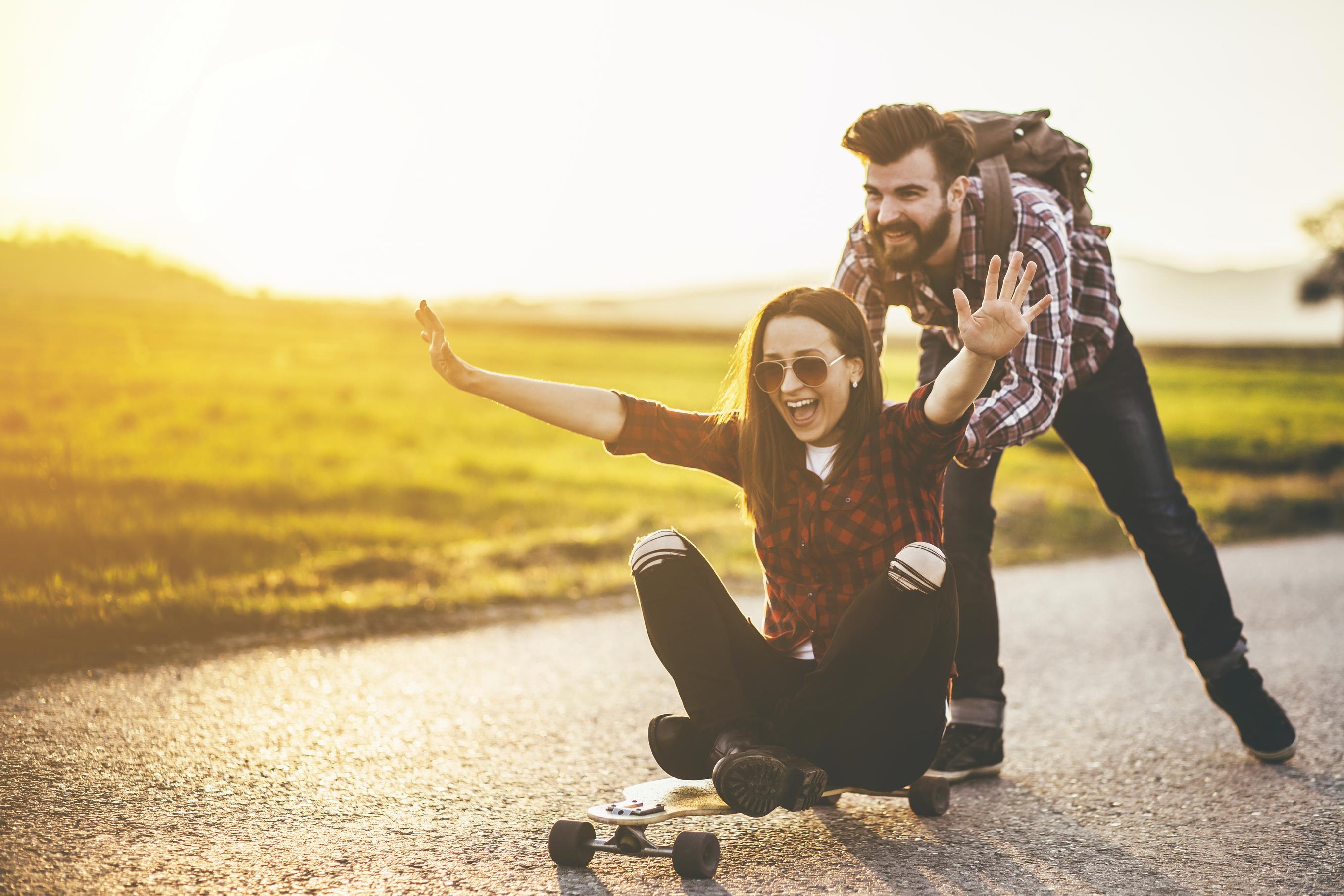 un novio empujando a su novia que esta sentada en una patineta