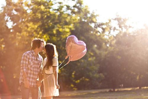 novios besándose en el parque con globo de corazón