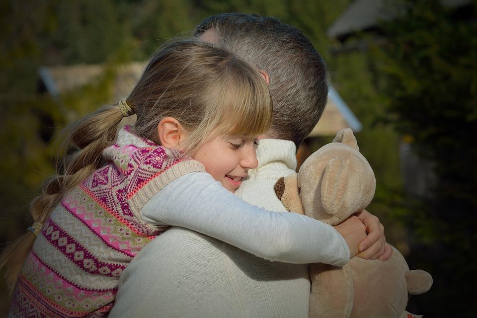 padre e hija con oso de peluche