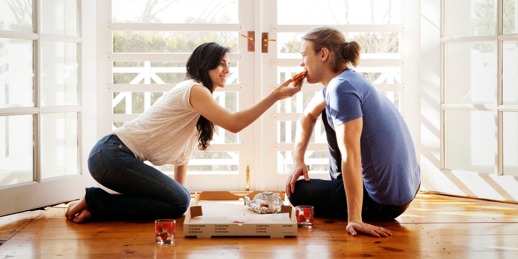 pareja comiendo pizza en el piso