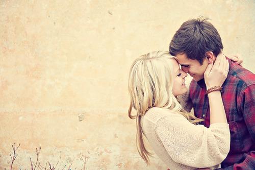 pareja feliz abrazados frente al muro