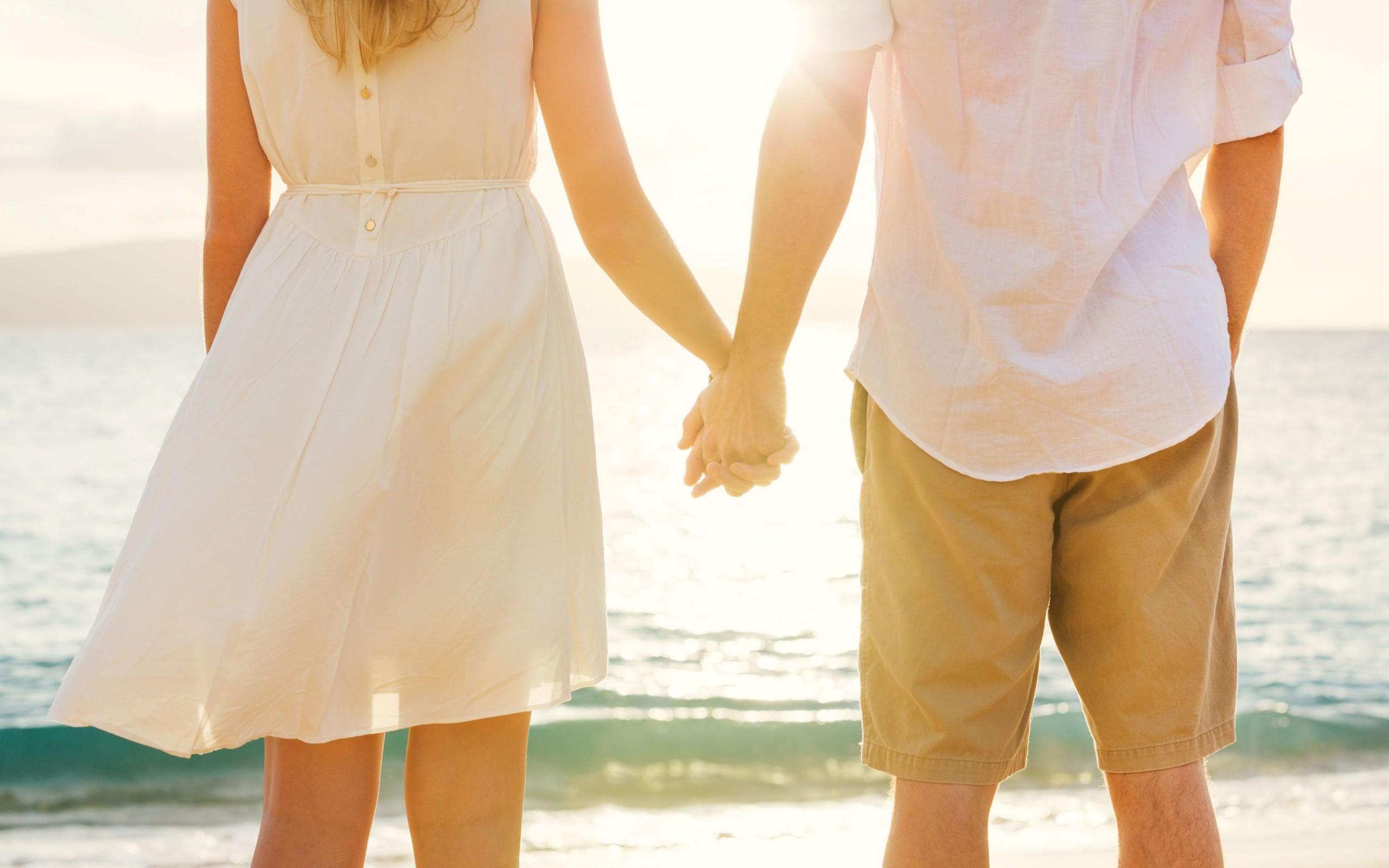 pareja tomada de la mano en la playa vestidos de blanco