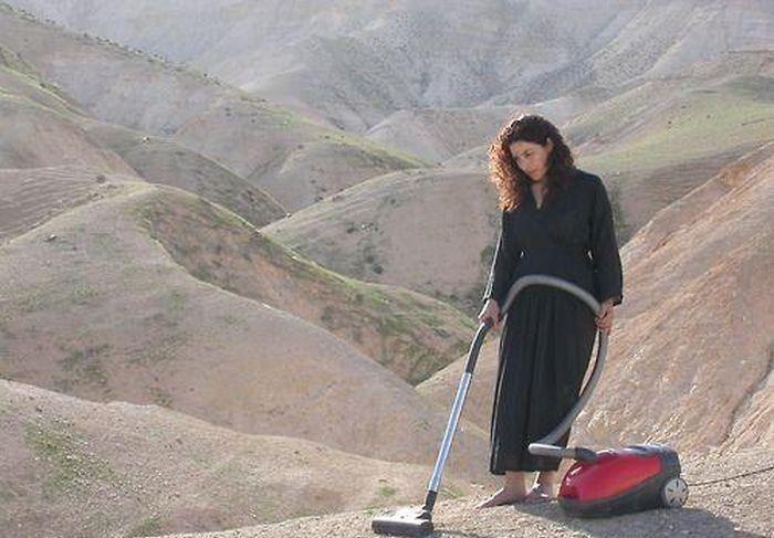mujer con aspiradora en desierto