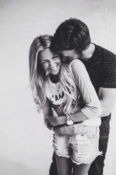 Chico abrazando a una chica por la cintura