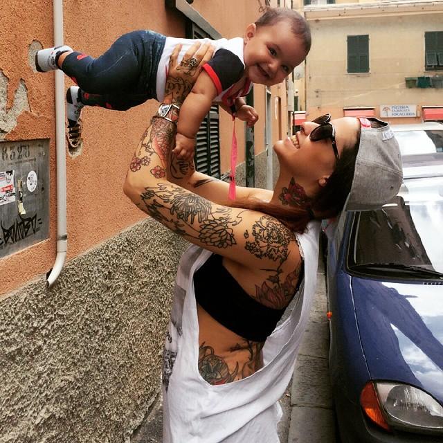 mujer con tatuajes cargando a bebé