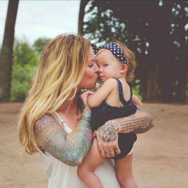 mujer rubia besando a una bebé