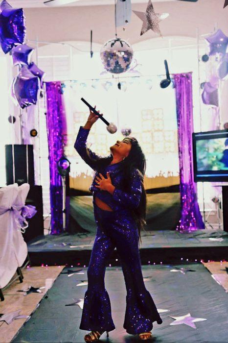 niña con ropa morada cantando