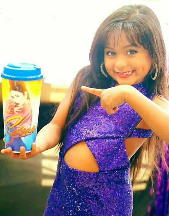 niña con traje morado y vaso