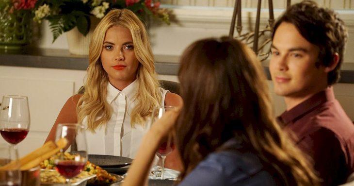mujer rubia entada en la mesa