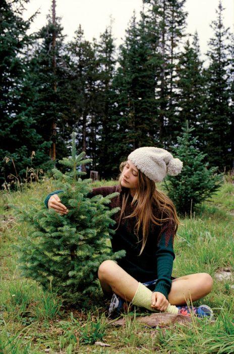 mujer rubia con gorro abrazando a un árbol
