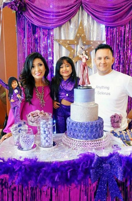 niña al lado de madre y padre con pastel