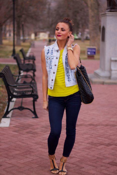 mujer con blusa amarilla y chaleco de mexclilla