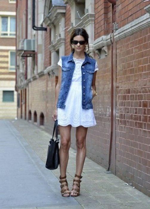 mujer con vestido blanco y chaleco de mezclilla