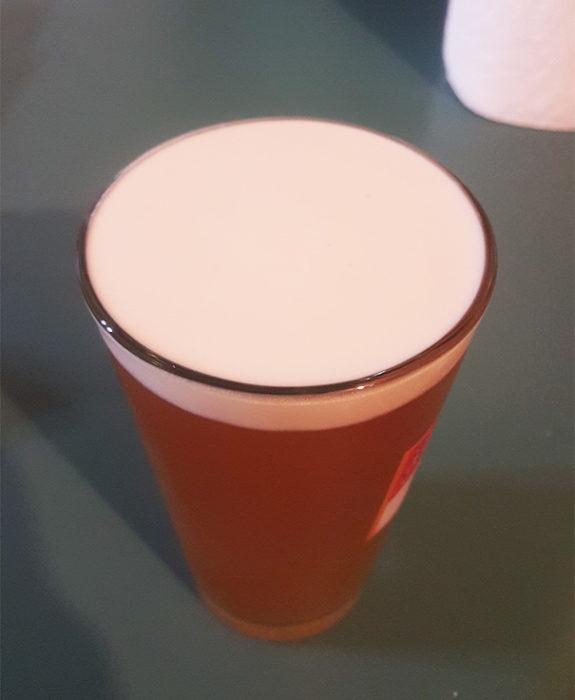 Espuma de la cerveza en perfecta simetría con un vaso