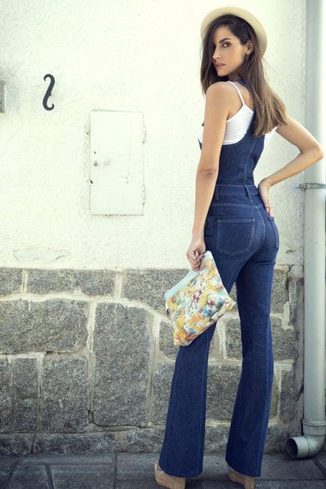 Chica usando un palazzo de mezclilla largo, sombrero y bolso de mano
