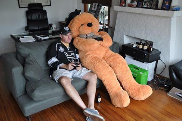 Hombre y oso de peluche gigantes jugando xbox