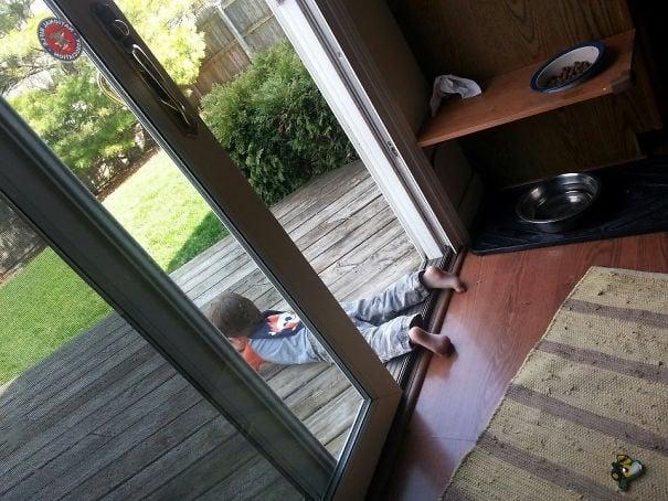 Niño con los pies dentro de la casa y el cuerpo afuera