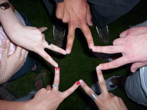 Personas formando una estrella con sus dedos