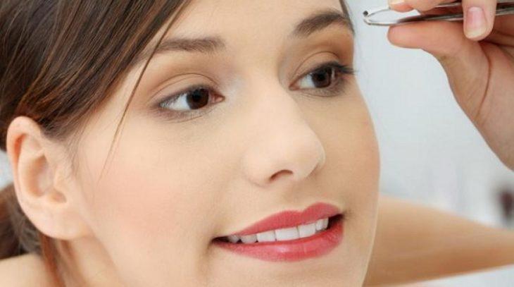 Chica depilando sus cejas