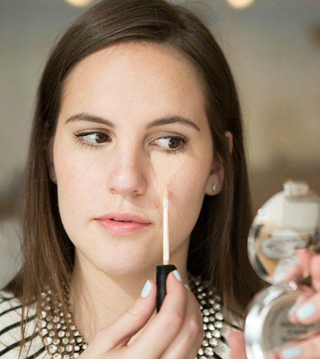 Chica aplicando maquillaje en sus pomulos