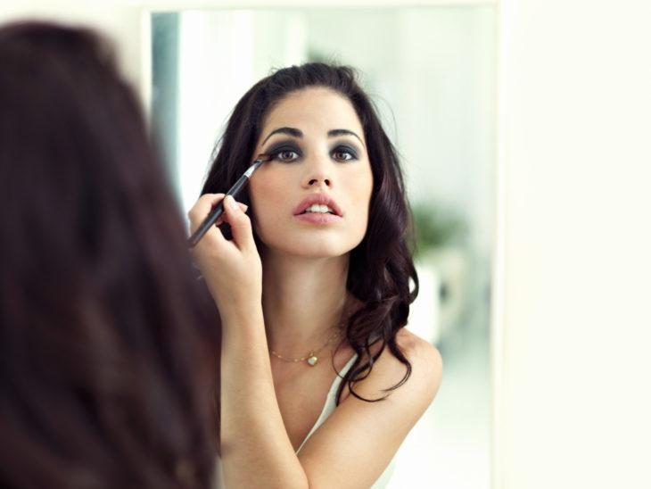 Chica maquillando sus ojos de color oscuro