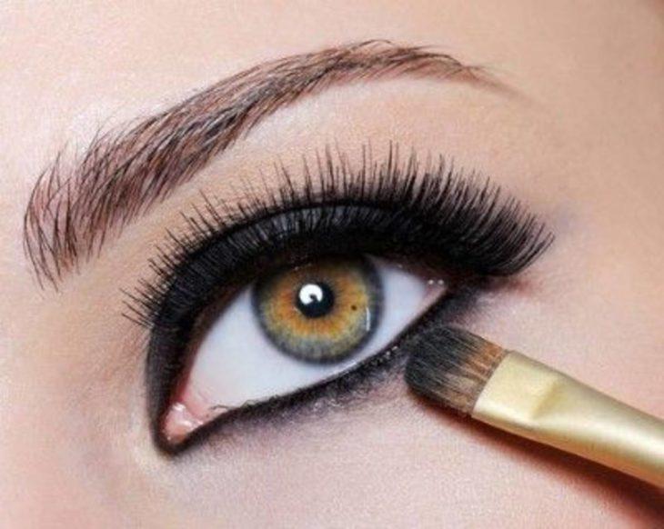 Chica aplicandose delineador en la parte inferior del ojo