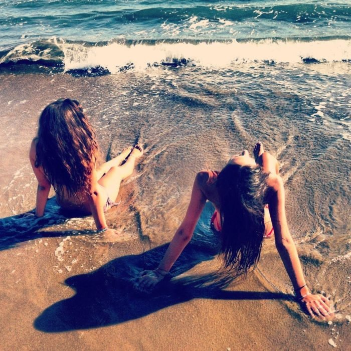 chica con amiga en la playa
