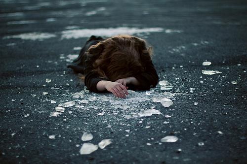 chica deprimida y ansiosa tirada en la calle con cristales