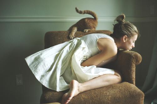 chica con ansiedad y depresión en un sillón con gato